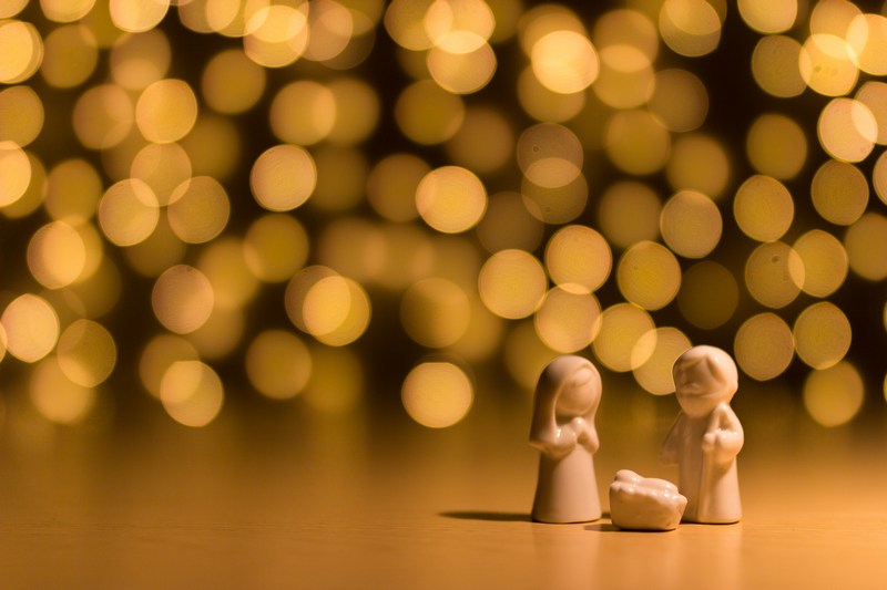 Little people figures standing around Baby Jesus