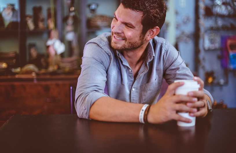 man smiling with coffee cup